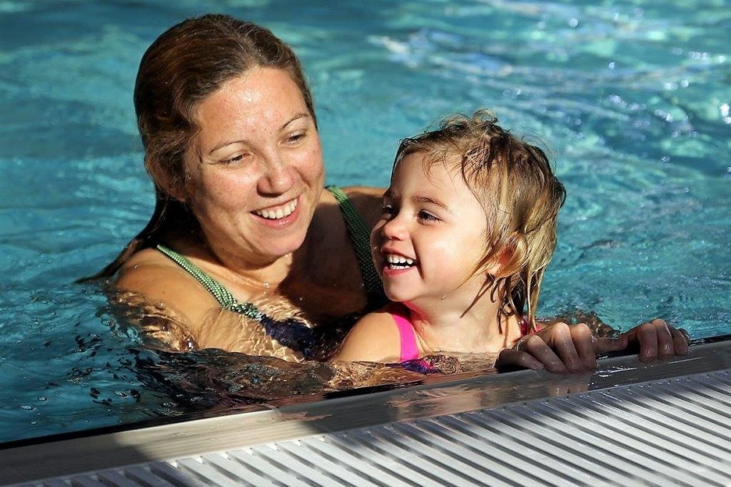 Mum bonding with child swimming